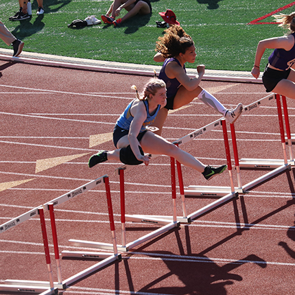 Sasquatch woman hurdler jumping over a hurdle against other opponent