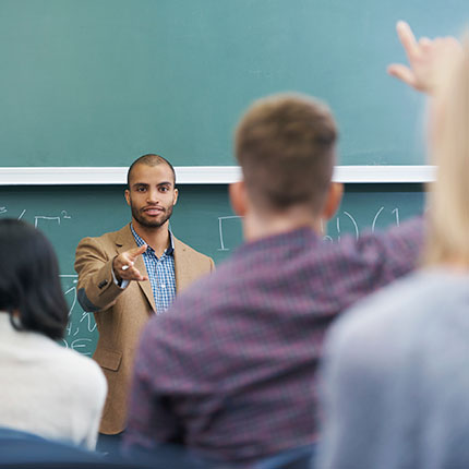 Teacher at front of class at chalkboard