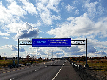 "A sign above the highway leaving the Spokane International Airport, with a thank you message that reads ""thank you for the generous 787 engine donation to Spokane Community College!"""