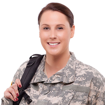 A woman in a military style outfit standing and smiling at the camera.