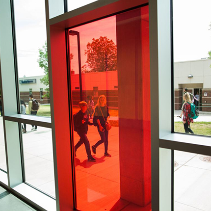 Two students walking behind a red pane of glass at Spokane Falls Community College