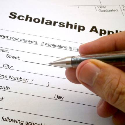 scholarship application being filled out with a pen