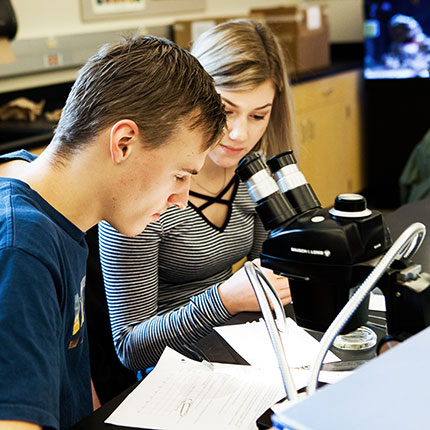Two students looking through microscope