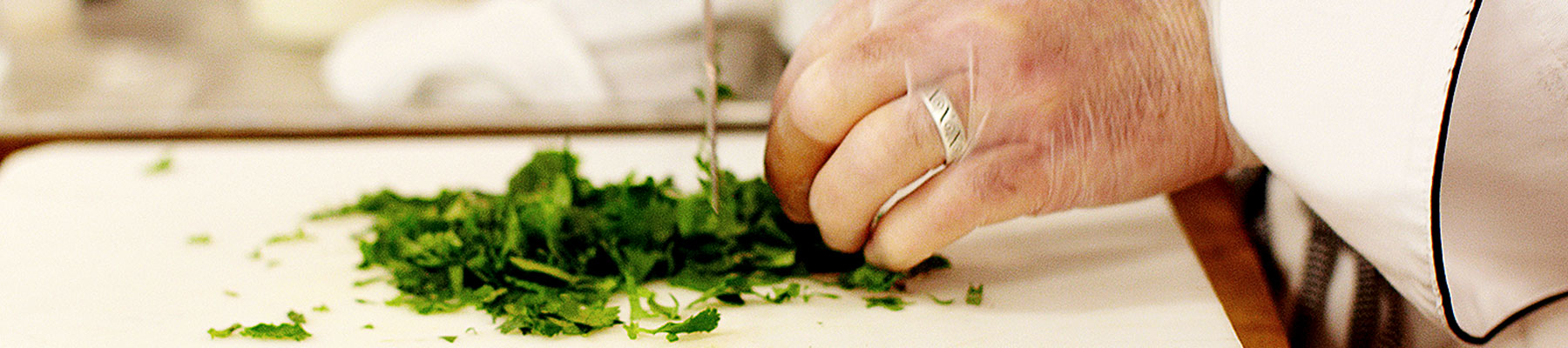 Close up of hands chopping cilantro