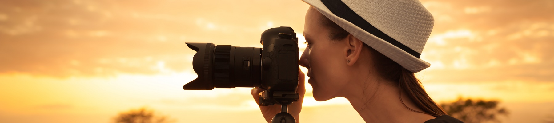 A woman using a camera at sunset