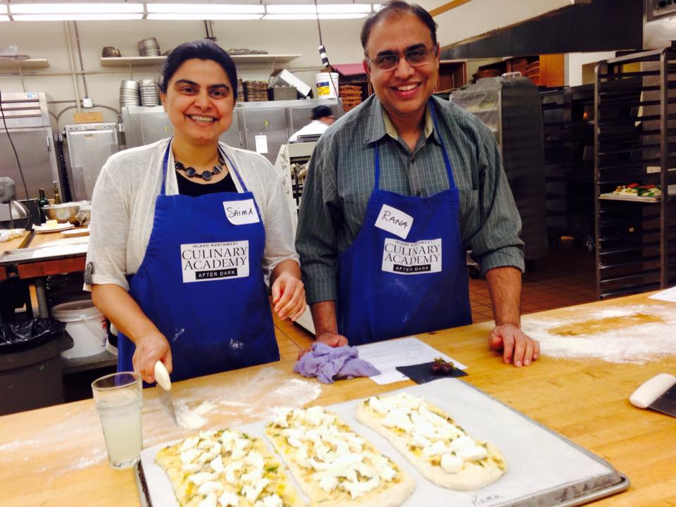 Couple making flatbread in teaching kitchen.