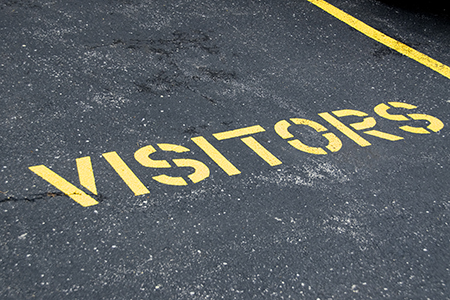 the word visitors painted on the asphalt for aparking space